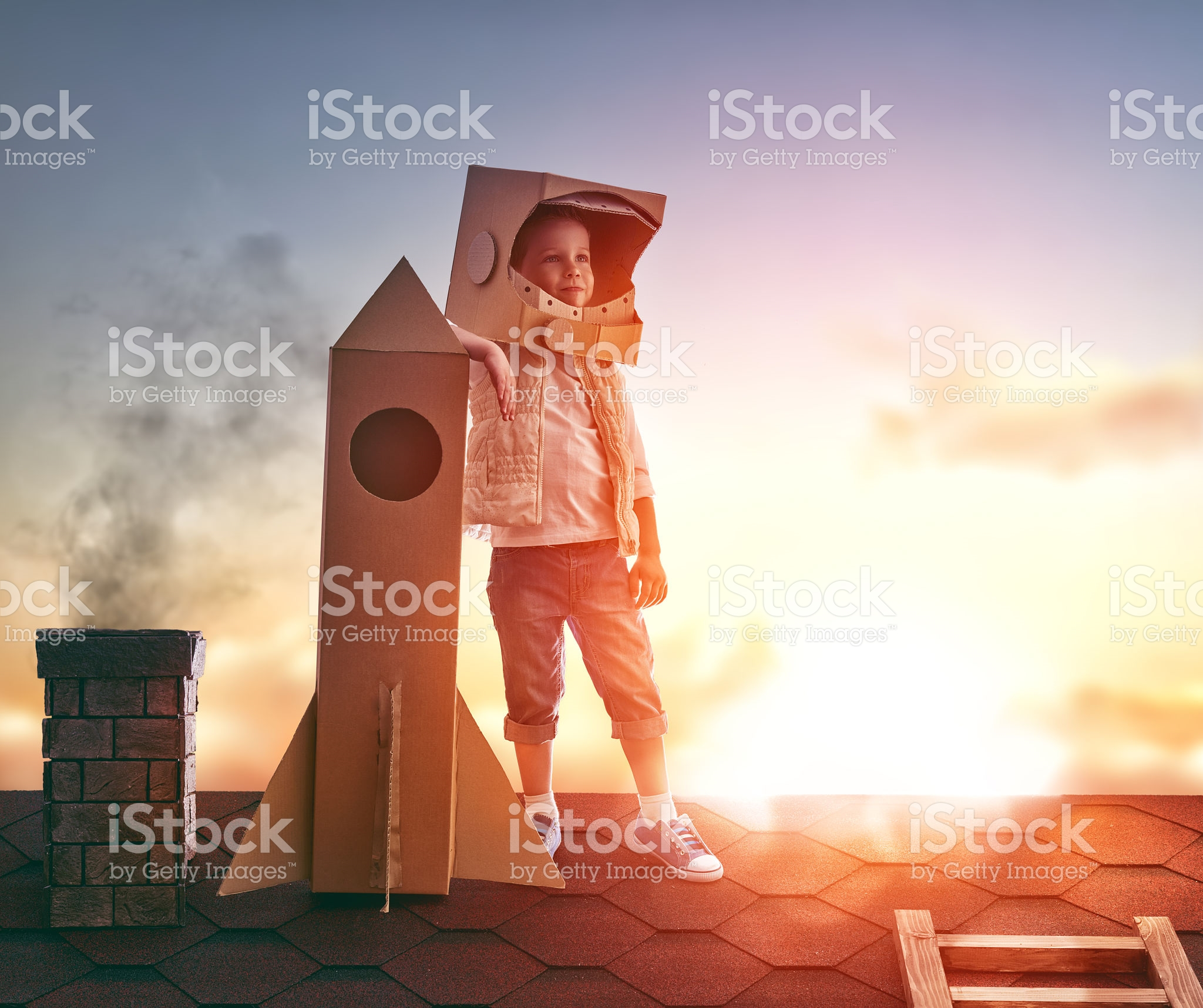 Little child boy plays astronaut. Child on the background of sunset sky. Child boy in an astronaut costume standing on the roof of the house and looking at the sky and dreaming of becoming a spaceman.